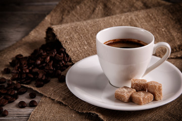 Espresso cup and saucer with brown cane sugar and coffee beans