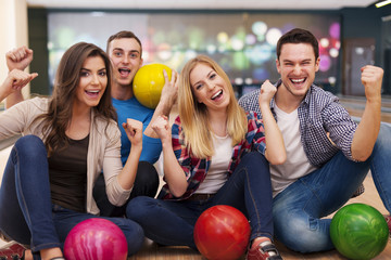 Portrait of smiling friends at the bowling alley.