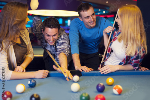 Group of four friends playing billiard