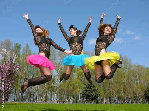 three cheerful showgirls jumping outdoors