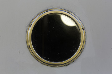 Metal porthole on white boat