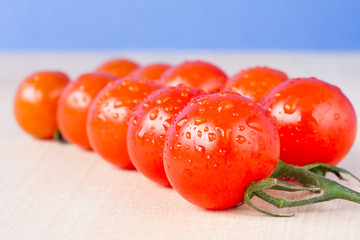 Ripe cherry vine tomatoes on  a table with blue sky background
