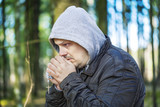 Religious man with a rosary in the woods