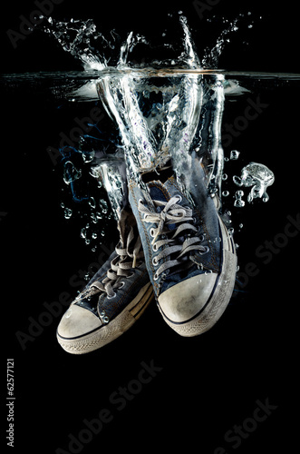 Splashing  old dirty sneakers on a black  background