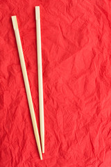 Chopsticks lay on a red napkin