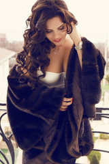 sexy glamour woman   in fur coat posing at the balcony