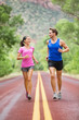 Two people jogging for fitness running on road