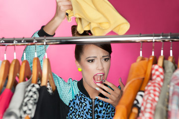 Surprised woman searching for clothing in a closet