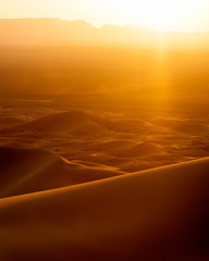 Image of sunset and speeding car from sand dunes in Morocco