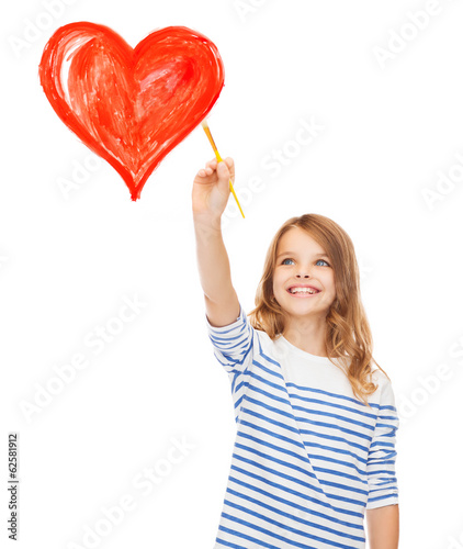 cute little girl drawing heart with brush
