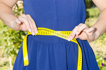 woman measuring waistline with centimeter