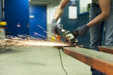 Industrial-Man hands sawing metal with sparks in workshop