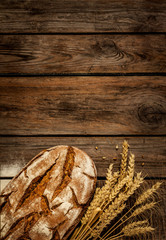 Rustic bread and wheat on vintage wood table