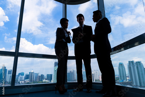 Businesspeople standing at office windo working