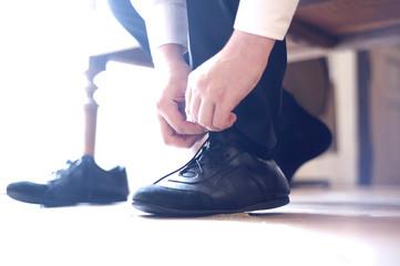 The groom puts on, ties laces on footwear