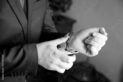 The groom,  man clasps a button at a jacket