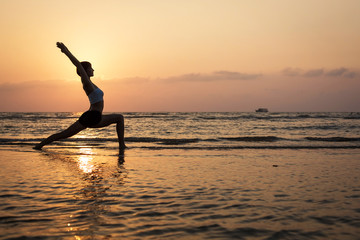 Yoga silhouette on the beach, virabhadrasana pose
