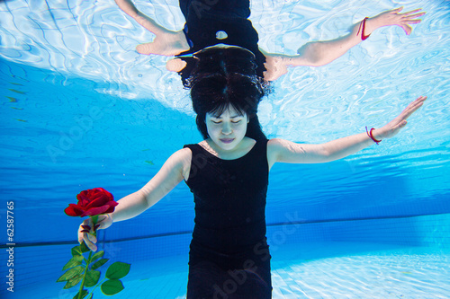 Beautiful young Asian woman  under the water with red rose