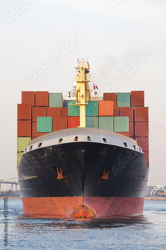 Cargo freight ship with stacked container at harbor terminal