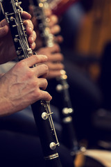 Human hands playing a clarinet closeup