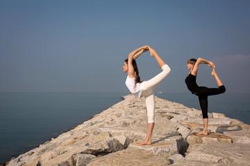 Beautiful young women practicing yoga on the beach. Natarajasana