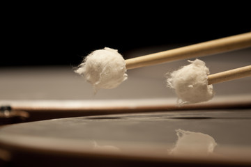 Drum sticks hitting the timpani closeup
