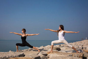 yoga on the beach. Virabhadrasana
