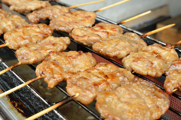 Pork skewers are cooked on a gas stove