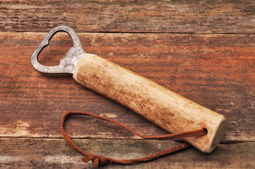 A bottle opener with a wooden handle
