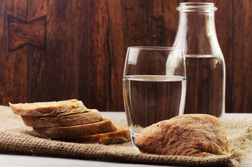 A glass bottle and a glass with water and sliced bread