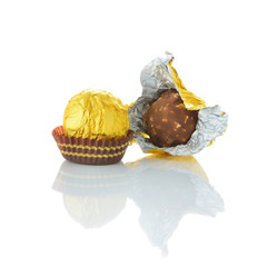 Two chocolate balls with almond in a gold foil paper. front view
