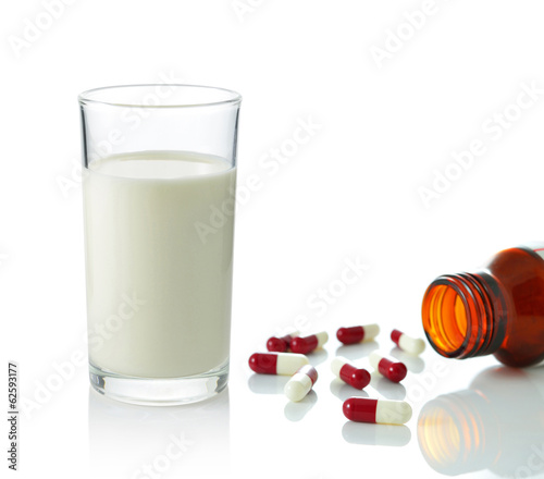 Red pill capsules with brown glass bottle and glass of milk isol