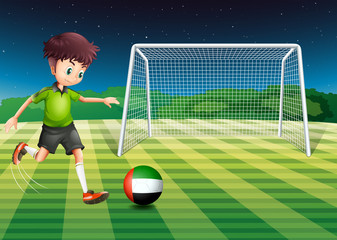 A male athlete kicking the ball with the flag of the United Arab