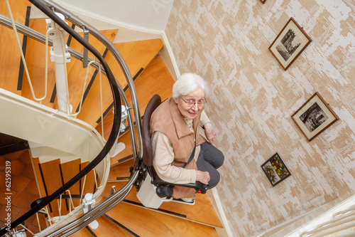 elderly woman using the stairlift - 62595319