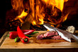 Delicious beef steaks on wooden desk and fire on background