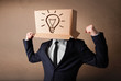 Businessman gesturing with a cardboard box on his head with ligh