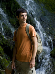 young man standing in front of waterfall
