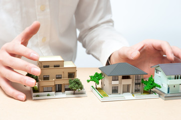 家の模型を持っている手