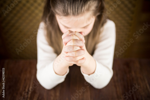 The girl prays at a table