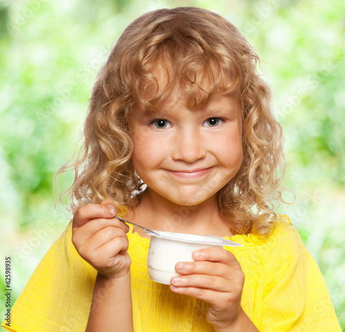 Little girl eating yogurt at summer