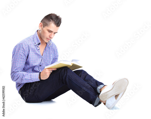 Young man sitting on floor and reading a book, isolated on white