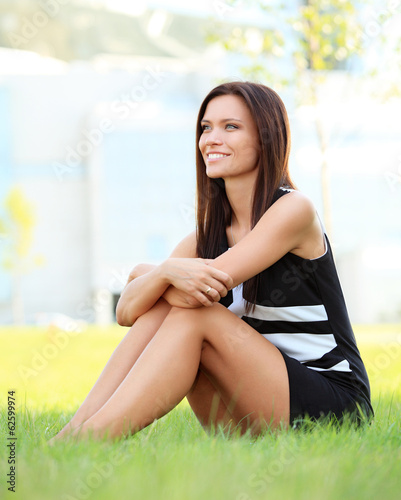 young smiling business woman outdoors sitting on the grass.