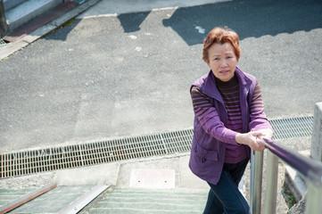 高齢の女性が階段を上り下りする様子