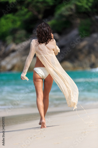 Srear view of sexy Slim woman walking at a beach