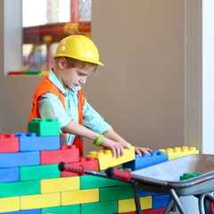 Happy boy in safety helmet playing indoors building house