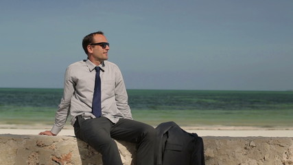 Businessman relaxing on stone wall by the sea