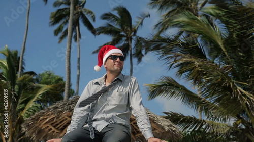 Funny young businessman in santa hat in exotic location