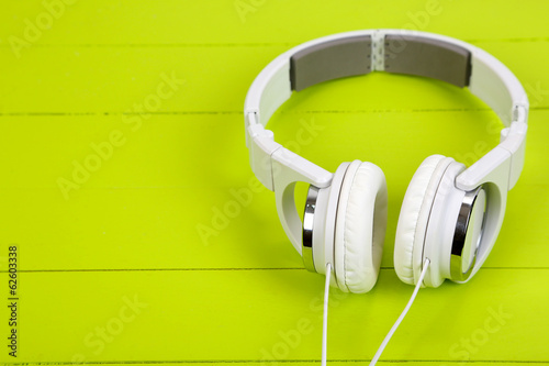 White headphones on wooden table close-up