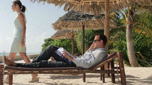 Business couple with cellphone and documents in exotic resort