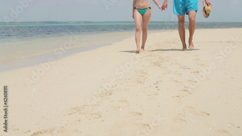 Couple in love holding hands, walking on beautiful exotic beach